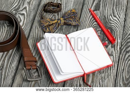 Accessories, Belt, Bow-tie, Notebook And Pen. Shot From Above, On Brushed Pine Boards.