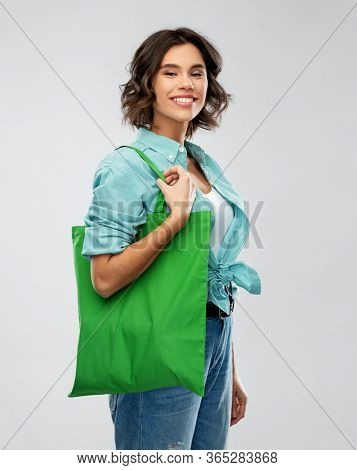 people concept - portrait of happy smiling young woman in turquoise shirt with green reusable canvas bag for food shopping on grey background