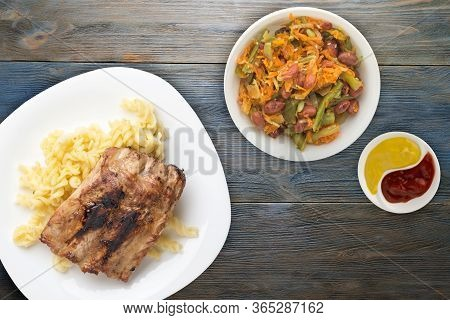 Grilled Pork Ribs With Pasta. Grilled Pork Ribs On A White Plate On A Blue Wooden Background. Grille