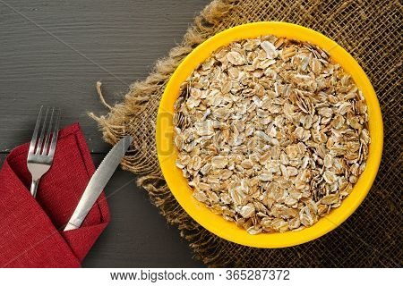 Muesli On A Dark Grah Wooden Table. Muesli On A Yellow Plate Whith Fork And Knife Top View . Healthy