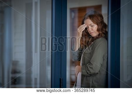 Stressed mature woman standing near window suffering from strong headache. Middle aged redhead woman with terrible migraine holding head with closed eyes. Mid lady feels pain in stomach, copy space.