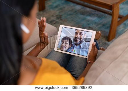 Rear view of indian mother doing a video call with her husband and son. Young woman in conversation with middle eastern man and smiling boy on digital tablet. Happy latin family in video conference.