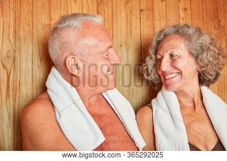 Happy seniors couple together in the sauna on wellness vacation