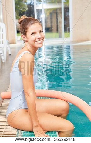 Young woman as a physiotherapist for aqua fitness and hydrotherapy by the pool