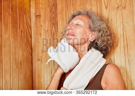 Old woman sweats in the healthy steam bath or sauna in the spa hotel