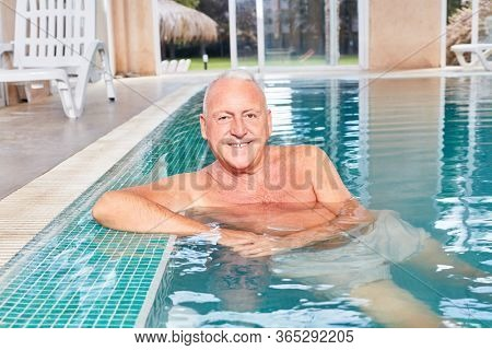 Smiling senior man as a vital retiree in the swimming pool at leisure
