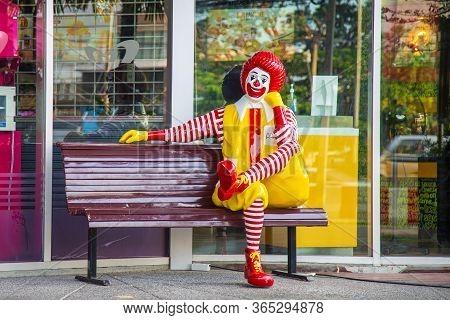 Nontaburi, Thailand- May 07, 2020 : Ronald-mcdonald Mascot Sitting On Wooden Bench In Front Of Mcdon