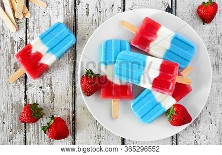 Plate Of Red, White And Blue Summer Fruit Popsicles. Overhead View Table Scene On A White Wood Backg
