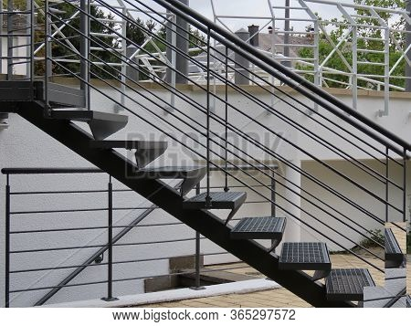 Fresh Painted Grey Metal Stairs And White Wall Of A Parking Lot, White Railings In Background, With