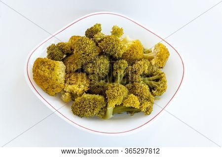 Boiled Yellowed Broccoli On A White Plate. Inflorescence Boiled Broccoli. Plate Of Broccoli On A Whi