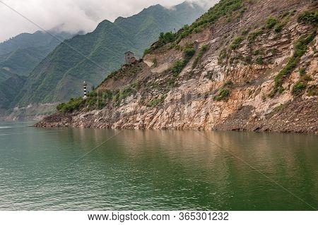 Shengli Street, China - May 6, 2010: Xiling Gorge On Yangtze River. Rocky Cliff Above Green Water Wi