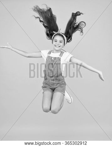 Small Girl Jump Yellow Background. Full Of Energy. Active Girl Feel Freedom. Fun And Relax. Feeling