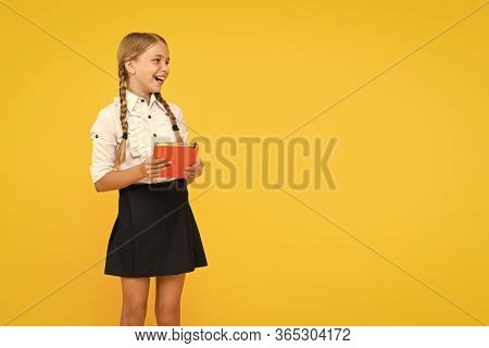 The Joy Of Good Knowledge. Cute Small Girl Holding Book On Yellow Background. Adorable Little School