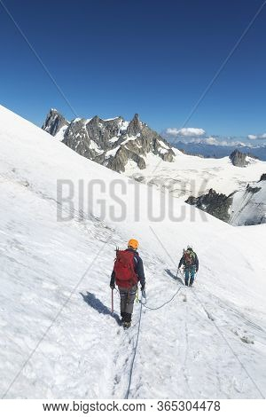 Alpinists With Rope And Climbing Tools On Col Du Midi In Front Of Grandes Jorasses, Mont Blanc Massi
