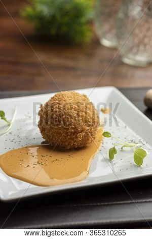 Arancini Made With Risotto And Stuffed Mozzarella On Sauce