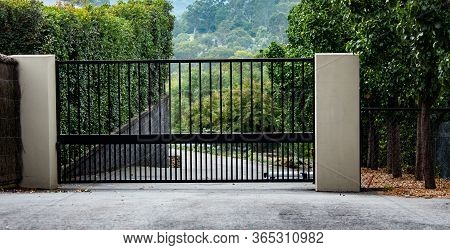 Black Metal Wrought Iron Driveway Property Entrance Gates Set In Brick Fence, Concrete Path, Garden