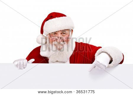 Santa Claus pointing in white blank sign with smile, isolated on white background