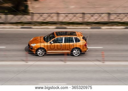 Moscow , Russia - April 30, 2020: Orange Porsche Cayenne Fast Moving On The City Road. Car Rushing O