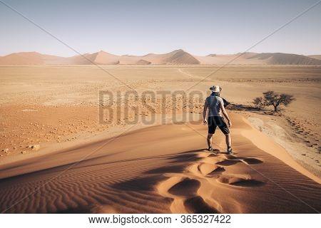 Namibia Namib Desert Sossusvlei Man Walking On The Top Of The Famous Dunes At Sunrise. Epic Intrepid