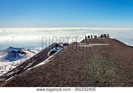 A Number Of Unidentified Hikers Enjoy The Breathtaking View From Etna Mountain, In Sicily, Italy.