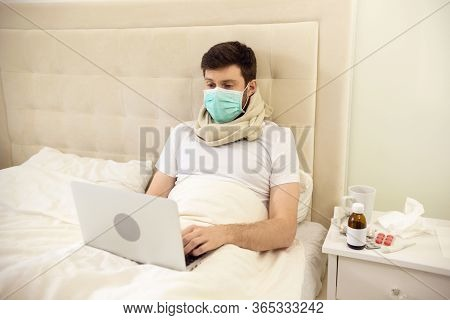 Sick Man Working In Bed Wearing Medical Mask. Man Working At Home. Man Using Laptop In Bed. Man Ill
