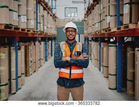 Successful Manufacturing Unit Worker Standing In Warehouse Distribution Centre With Folded Hands Wit