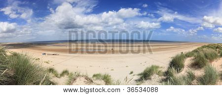 People enjoying summmer day on the beautiful sandy beach of Holkham in North Norfolk England poster
