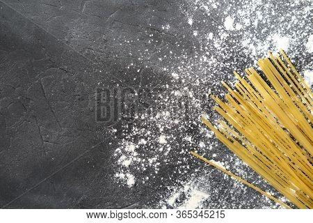 Yellow Long Spaghetti On Grey Background With Flour. Yellow Italian Pasta. Long Spaghetti. Raw Spagh