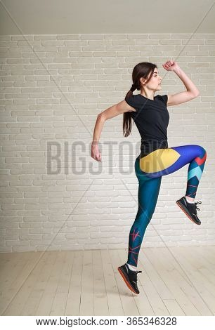 Active Athletic Slim Young Woman Runner Doing Stretching Exercises Jumping At Home On The Brick Wall