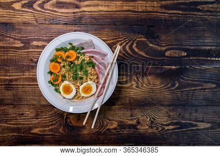 A Plate Of Japanese Ramen With Chopsticks Stands On A Wooden Table. Japanese Ramen. Wooden Backgroun