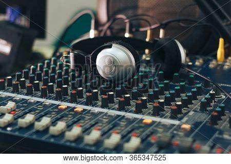 Silver Headphones On A Studio Audio Mixer.