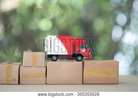 Miniature Cargo Car Put On Miniature Brown Box. Concept Of Delivery Cargo