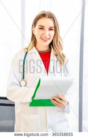 Female Beautiful Wearing A Doctor Uniform Have A Stethoscope And Holding A Green Paper Chart And Smi