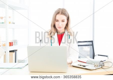 Female Beautiful Wearing A Doctor Uniform Using A Notebook Computer And Talking Case Of Treatment.