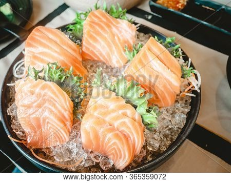 Sashimi Consists Of Raw Salmon Fish Slice Placed On The Ice In A Black Ceramic Cup In A Restaurant.