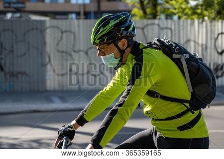Ukraine, Kyiv - April 25, 2020: Professional Bicycle Rider Rides Wearing A Medical Mask To Prevent O