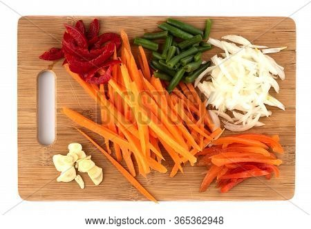 Sliced Onions, Garlic, Carrots, Sweet Peppers On A Cutting Board. Sliced Vegetables On A Cutting Boa
