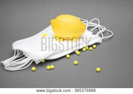 A Yellow Lemon Is Lying On A Pile Of Medical Masks. Ascorbic Acid Vitamins Are Scattered Nearby. Con