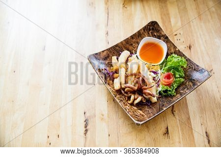 Fried Squids In Wood Plate.steamed Squid Fried With Salty Sauce Thai Food.grilled Squid And Vegetabl