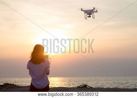 Girl Piloted Uav Copter Drone Flying At Sunset.drone Copter Flying With Digital Camera. Uav Drone Wi