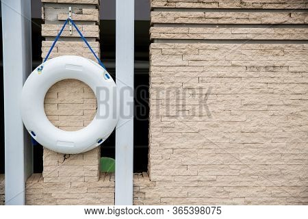 Lifebuoy, All Water Rescue Emergency Equipment. White Lifebuoy On Brick Wall. Nearby The Swimming Po