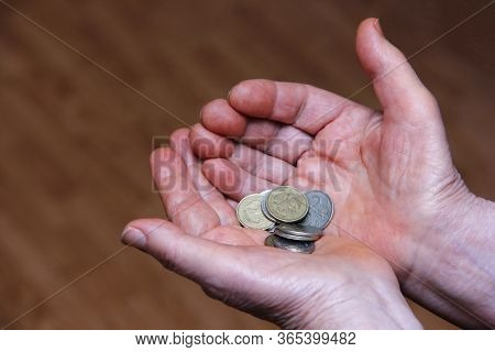 Russian Rubles In Coins In The Hands Of An Elderly Person. Below The Breadline. Pension Reform Conce