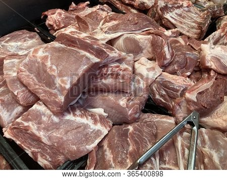 Close Up Of Large Chunks Of Raw Pork Meat In Refrigerator On Supermarket Counter.