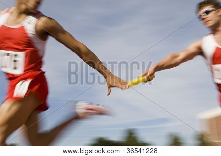 Blurred motion male runners passing baton in relay race