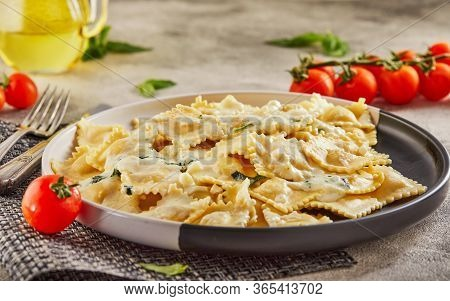 Tasty Cooked Ravioli With Cream Sauce, Cherry Tomatoes, Sunflower Oil And Basil On A Light Wooden Ba