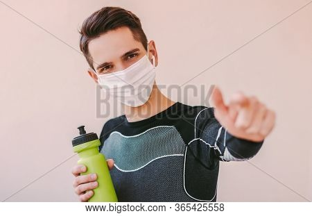 Confident Sports Man In Medical Face Mask Pointing With Index Finger And Listening Music. Happy Youn