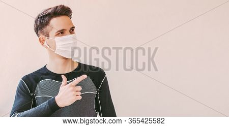 Young Confident Sports Man In Medical Face Mask Pointing With Finger To Background With Copy Space.