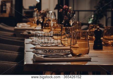 Row Of Tables Set Inside A Restaurant, Moody Light, Shallow Focus.
