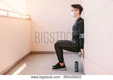Young Sporty Man Fitness Coach In Medical Face Mask Squatting Against Wall On Balcony. Confident Spo