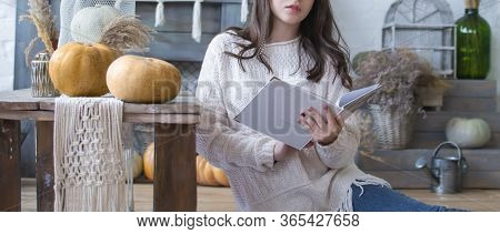 Close-up. The Girl Is Sitting On The Floor And Reading A Book. Near On The Table Are Pumpkins. Hallo